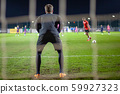 Goalkeeper catch the ball when defensive on goal during a football match 59927323