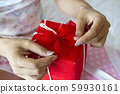 Selective focus female hand tied bow gift box 59930161