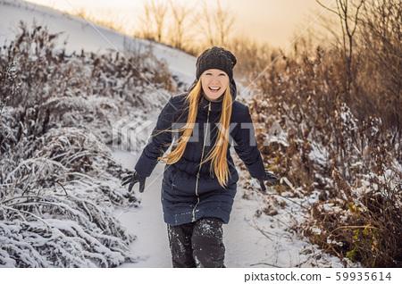 Woman has fun in winter, throws snow 59935614