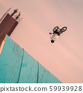 Young unrecognizable Bmx rider performing air trick back flip. Extreme sport. Intentional angle to 59939928