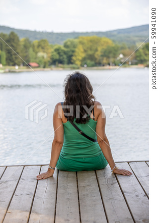 Woman sitting on a pier in front of lake Orfu , in 59941090