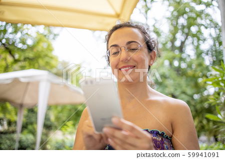 Pretty Spanish woman with mobile phone smiling 59941091