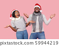 Excited Christmas man and woman gesturing over pink background 59944219