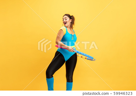 Young caucasian plus size female model's training on yellow background 59946323