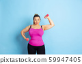 Young caucasian plus size female model's training on blue background 59947405
