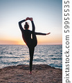 Slim woman in black bodysuit practicing yoga near sea or ocean during sunrise light. Flexibility, stretching, fitness, healthy lifestyle.  59955535