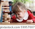 Caucasian little girl hand hold magnifier lens. 59957007
