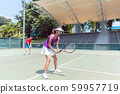 Confident female tennis player waiting to hit the ball during doubles match 59957719