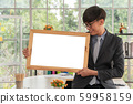 Happy Asian young businessman holding an empty 59958159