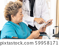 Doctor using tablet with old patient 59958171