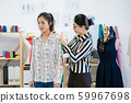 female tailor measuring asian woman client 59967698