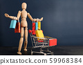 Cheerful happy shopaholic wooden doll with lots of shopping bags on arm and shopping cart 59968384