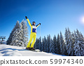 Happy woman posing on skis before skiing. Sunny day at ski resort. Clear blue sky, snow-covered fir trees on background. 59974340