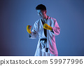 Confident korean man in kimono practicing hand-to-hand combat, martial arts 59977996