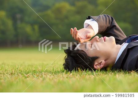 Businessman park lie down 59981505