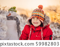 Cute boy in red winter clothes builds a snowman. Winter Fun Outdoor Concept 59982803