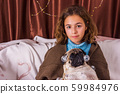 Chistmas garland on pug dog. Charming girl with a 59984976
