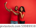 Young emotional african-american man and woman on red background 59989938