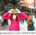 Beautiful and happy girl smiles, winter outdoors, background trees Christmas trees snow drifts. Snowboard for skiing board. Mask for riding glasses. Resting at winter resort at weekend. 59991084