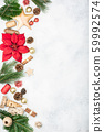 Christmas background. Top view of fir tree branches, brown gift boxes, various packing accessories, pinecones, wooden decorations, tags on off white concrete table, copy space, selective focus 59992574
