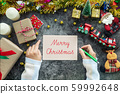 hand writing Merry Christmas on greeting card during Christmas season and gift festival, decorations with Christmas ornament on table 59992648