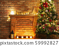 Beautiful decorated fireplace, wooden mantelpiece with fairy lights, handmade ornaments, candles and lantern, Christmas tree to the side, selective focus 59992827