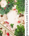 Top view of handmade Christmas wreath, wrapping paper, presents, pinecones fir branches on wooden table, selective focus 59992852