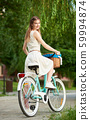 Beautiful female holds bicycle with basket at greenery background of city park 59994874