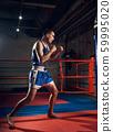 Handsome kick boxer training kicking and punching boxing bag 59995020