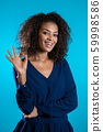 Young woman making OK sign over blue background. Winner. Success. Positive young african girl smiles for camera 59998586