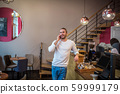 Bearded man speaking with wife over phone while waiting for order 59999179