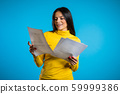 Pretty latin female checks documents, utility bills. Serious woman standing on blue background. She is satisfied, smiling, 59999386