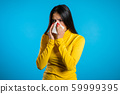 Young hispanic girl sneezes into tissue. Isolated woman is sick, has a cold or has allergic reaction. Health, medicine, illness, treatment concept 59999395