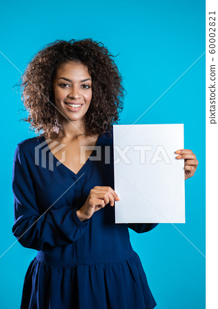 African american woman holding white a4 paper poster. Copy space. Smiling pretty girl with curly hairstyle on blue background. 60002821