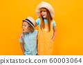 Two surprised red-haired friends are looking in summer hats, looking to the side against over yellow 60003064