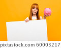 red-haired girl holding a piggy bank and a banner in hands over yellow background 60003217