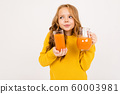 cute girl holding a glass and a jug with carrot juice on an isolated white background 60003981