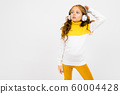 young girl in a yellow and white sweater listens to music and looks into the distance on a white 60004428