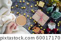 hand holding a cup of hot coffee in winter season with Christmas background decorations and gift boxes on table 60017170