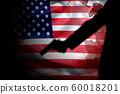 handgun in gunman hand with blood stain on American flag. reform gun control in America concept 60018201