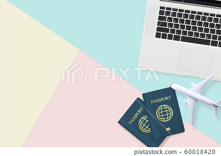 flat lay of passport , white plane model and computer laptop on pastel blue ,yellow and pink color background with copy space. travel , visa and vacation concept 60018420