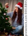 Happy woman in santa hat decorates New Year tree 60018805
