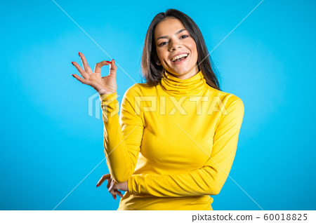 Young woman making OK sign over blue background. Winner. Success. Positive brunette young hispanic girl smiles for camera. 60018825