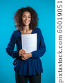 African american woman holding white a4 paper poster. Copy space. Smiling pretty girl with curly hairstyle on blue background. 60019051