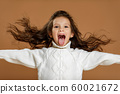 little child girl in white sweater showing her tongue 60021672