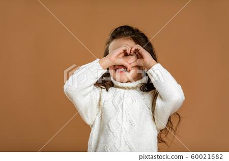 little child girl in white sweater making heart-shape gesture 60021682