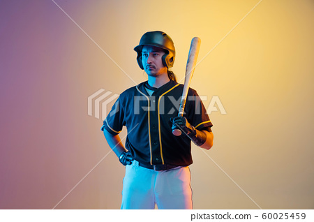 Baseball player, pitcher in a black uniform practicing on gradient background in neon light 60025459