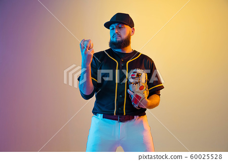 Baseball player, pitcher in a black uniform practicing on gradient background in neon light 60025528