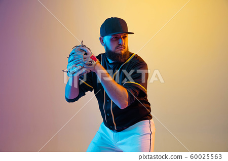 Baseball player, pitcher in a black uniform practicing on gradient background in neon light 60025563