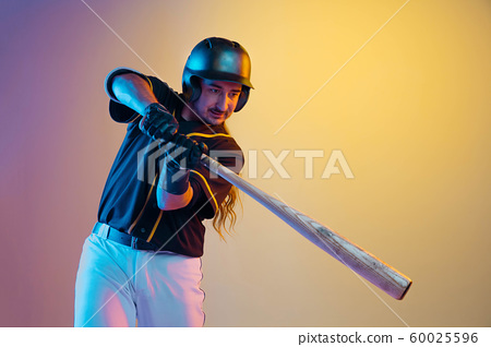Baseball player, pitcher in a black uniform practicing on gradient background in neon light 60025596